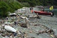 プラスチックごみが漂着した佐田岬半島の浜辺に水陸両用ボートで上陸した=愛媛県伊方町で2018年7月4日、小松雄介撮影