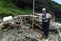 佐田岬半島の浜辺で漂着ごみの層を測るE.Cオーシャンズの岩田功次代表理事。露出している部分は1㍍ほどの厚さがあった=愛媛県伊方町で2018年7月4日、小松雄介撮影