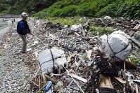 佐田岬半島の浜辺に漂着したプラスチックごみを調査するE.Cオーシャンズのメンバー=愛媛県伊方町で2018年7月4日、小松雄介撮影