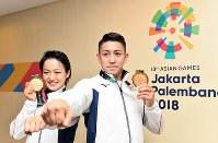 金メダルを手に記念撮影に応じる空手の男子形優勝の喜友名諒(右)と女子形優勝の清水希容=ジャカルタで2018年8月25日、宮間俊樹撮影