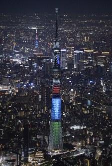 東京パラリンピック開催まで2年となり、シンボルマークの赤、青、緑色にライトアップされた東京スカイツリー(手前)と東京タワー=東京都墨田区で2018年8月25日午後7時7分、本社ヘリから