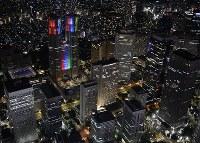 東京パラリンピック開催まで2年となりライトアップされ新宿の高層ビル群から浮かび上がる東京都庁(左上)=東京都新宿区で2018年8月25日午後7時19分、本社ヘリから