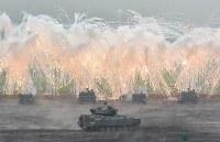 富士総合火力演習で発煙弾を発射する陸上自衛隊の装甲車など=静岡県御殿場市の東富士演習場で26日、前谷宏撮影
