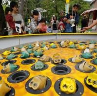 観覧車のほかにもレトロな遊具がいっぱい。鍋に入ったカエルを釣るアトラクションで白熱する家族連れ=北海道函館市の函館公園こどものくにで2018年8月19日、貝塚太一撮影