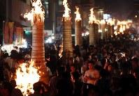 燃えさかるたいまつの周りを行き交う人たち=山梨県富士吉田市で2018年8月26日午後7時20分、小川昌宏撮影