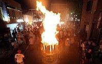 燃えさかるたいまつの周りを行き交う人たち=山梨県富士吉田市で2018年8月26日午後7時16分、小川昌宏撮影
