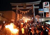 燃えさかるたいまつの周りを行き交う人たち=山梨県富士吉田市で2018年8月26日午後7時12分、小川昌宏撮影
