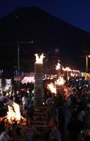 燃えさかるたいまつの周りを行き交う人たち。奥は富士山=山梨県富士吉田市で2018年8月26日午後6時49分、小川昌宏撮影