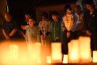 犠牲者を悼んで並べられたキャンドルの前で黙とうする人たち=広島市安佐南区で2018年8月20日午前4時13分、久保玲撮影