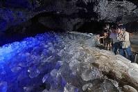 氷が貯蔵された鳴沢氷穴で、一時の涼しさを楽しむ人たち=山梨県鳴沢村で、小川昌宏撮影