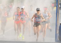 女子マラソンのコース中に設置されたミストシャワーの下を通る2位に入った野上恵子(手前)=ジャカルタで2018年8月26日、宮間俊樹撮影