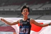 2位でフィニッシュし日の丸を手に観客の声援に応える野上恵子=ジャカルタで2018年8月26日、宮間俊樹撮影