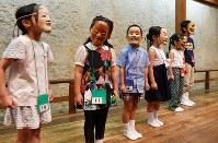 本物の能面をつけて、舞台に立つ子供たち=大阪市中央区で、望月亮一撮影