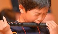 なかなかうまく音が出ず、真剣に笛に息を吹きかける男の子=大阪市中央区で、望月亮一撮影