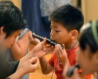 なかなかうまく音が出ず、一生懸命笛に息を吹きかける男の子=大阪市中央区で、望月亮一撮影