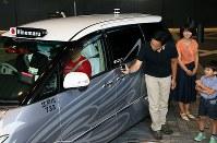 自動運転タクシーの公道営業実証実験で、スマ―トフォンをかざして解錠する一般公募で選ばれた親子=東京都千代田区で2018年8月27日午前9時5分、玉城達郎撮影