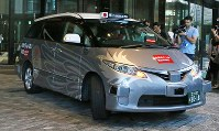 世界初の公道営業実証実験を行う自動運転タクシー=東京都千代田区で2018年8月27日午前8時10分、玉城達郎撮影