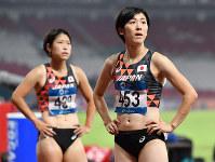 陸上女子100メートル障害決勝、レース後、記録を見つめる7位の紫村仁美。後方は5位の青木益未=ジャカルタのブンカルノ競技場で2018年8月26日、徳野仁子撮影