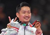 空手男子組手84キロ級、2連覇を果たし、金メダルを手にVサインを作る荒賀龍太郎=ジャカルタで2018年8月27日、徳野仁子撮影