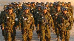 初の「戦地」入りとなるイラクのサマワ到着を報告するため、行進する陸上自衛隊本隊の先発隊員=サマワ駐留オランダ軍宿営地で2004年2月8日、岩下幸一郎撮影