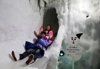 氷のコースを滑り下りる。出口直前の急降下に歓声が上がる=北海道上川町の「北海道アイスパビリオン」で2018年8月15日、貝塚太一撮影