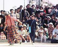 路上公演をする道化師のウインピーに連れ出され、照れ笑いする男の子=1970年