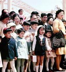 路上で繰り広げられる移動芸能を見る子どもたち=エキスポランドで1970年