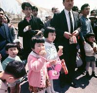 ソフトクリームを食べながら路上の移動芸能を見る子どもたち=エキスポランドで1970年