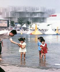人工池で水遊びする子どもたち。奥はスイス館=1970年