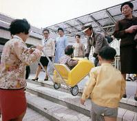 子どもを乗せたままのチャイルドカーを、警備員も手伝って階段を上げる=1970年