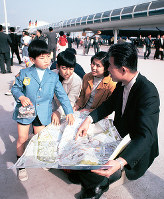 会場マップを広げる家族連れ=1970年