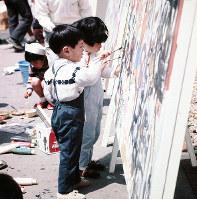 わんぱく広場のらくがきコーナーで、夢中で絵を描く子どもたち=エキスポランドで1970年