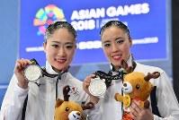 【アーティスティックスイミング】 デュエットで2位に入り銀メダルを手にする乾友紀子(右)、吉田萌=ジャカルタで2018年8月28日、宮間俊樹撮影