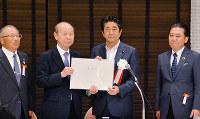 安倍晋三首相(中央右)に要望書を手渡す石井隆一富山県知事(同左)=富山市で、森野俊撮影