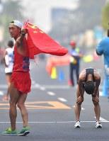 【アジア大会・陸上】陸上男子20キロメートル競歩、2位でフィニッシュし肩を落とす山西利和(右)。左は優勝した中国の王凱華=ジャカルタで2018年8月29日、徳野仁子撮影