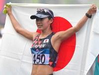 【アジア大会・陸上】陸上女子20キロメートル競歩、3位でフィニッシュし日の丸を掲げる岡田久美子=ジャカルタで2018年8月29日、徳野仁子撮影