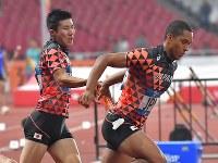 【陸上】陸上男子400メートルリレー予選、第3走者の桐生祥秀(左)からバトンを受け取るケンブリッジ飛鳥=ジャカルタのブンカルノ競技場で2018年8月29日、徳野仁子撮影