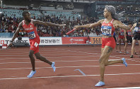 Bahrain's Salwa Naser, right, hands the baton to teammate Abbas Abbas during the mixed 4x400m relay final at the athletics competition at the 18th Asian Games in Jakarta, Indonesia, on Aug. 28, 2018. (AP Photo/Lee Jin-man)