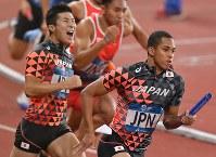 陸上男子400メートルリレー決勝で日本の第3走者の桐生祥秀(左)からバトンを受けるアンカーのケンブリッジ飛鳥=ジャカルタで2018年8月30日、宮間俊樹撮影