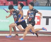 陸上男子400メートルリレー決勝で日本の第2走者の多田修平(左)にバトンを渡す第1走者の山県亮太=ジャカルタで2018年8月30日、宮間俊樹撮影