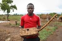 ジョン・タバンさん(18)。伝統楽器「アドゥング」。居住区に来てから自分で作った。教会の祈りで歌うときなどに使っている=ウガンダ・ユンベのビディビディ難民居住区で2018年4月7日、小川昌宏撮影
