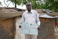 マニョン・ブレンさん(34)。大学の卒業証明書。南スーダンから持ってきた。大学ではビジネスを学んだ=ウガンダ・アルアのライノ難民居住区で2018年4月11日、小川昌宏撮影