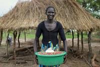 デボラ・アヤンさん(20)。配布されたばかりの豆。居住区に到着したばかりで、初めての食料。これで1ケ月分という=ウガンダ・アルアのライノ難民居住区で2018年4月11日、小川昌宏撮影
