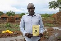 アヤン・エリッサさん(43)。南スーダンから持ってきた自分たちの民族「ケリコ」の教科書。南スーダンでは教師だった=ウガンダ・ユンベのビディビディ難民居住区で2018年4月7日、小川昌宏撮影