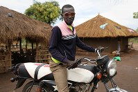 モーゼス・アニュメさん(18)。バイク。南スーダンから乗って避難した。居住区でもバイクタクシーとして収入も得ている=ウガンダ・ユンベのビディビディ難民居住区で2018年4月7日、小川昌宏撮影