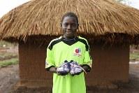 ケネディ・オブキさん(12)。支援団体からもらったサッカーシューズ。チリのサンチェス選手がお気に入りという=ウガンダ・ユンベのビディビディ難民居住区で2018年4月7日、小川昌宏撮影