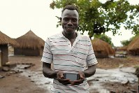 ドラバ・ニコラスさん(26)。スマートフォン。南スーダンから持ってきた。コンゴ民主共和国に避難した家族との連絡に使っている=ウガンダ・ユンベのビディビディ難民居住区で2018年4月7日、小川昌宏撮影