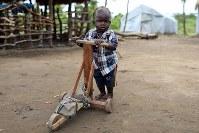 ヴィクトリア・マンディちゃん(10カ月)。木のおもちゃ。祖父が居住区の家具店で買ってくれた=ウガンダ・アルアのライノ難民居住区で2018年4月8日、小川昌宏撮影