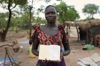 メリー・アモコシャンさん(21)。ディンカ語の聖書。出身民族「ディンカ」の言葉で書かれている。毎日、教会に通っている=ウガンダ・アルアのライノ難民居住区で2018年4月11日、小川昌宏撮影
