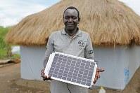 ジャスティン・バカタさん(62)。ソーラー発電機。居住区で購入した。ジュバに住む家族と話す携帯電話の充電に使っている=ウガンダ・アルアのライノ難民居住区で2018年4月8日、小川昌宏撮影